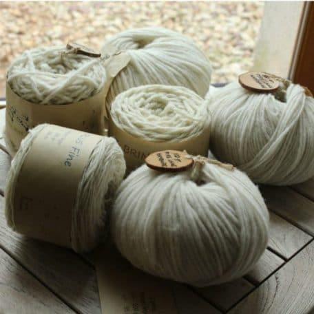 gamme de fils en pelotes de pure laine de différentes grosseurs de l'atelier pure laine