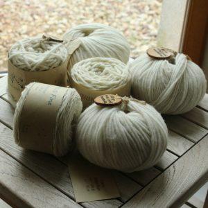 Pelotes écrue de grosseurs différentes de la marque Atelier pure laine